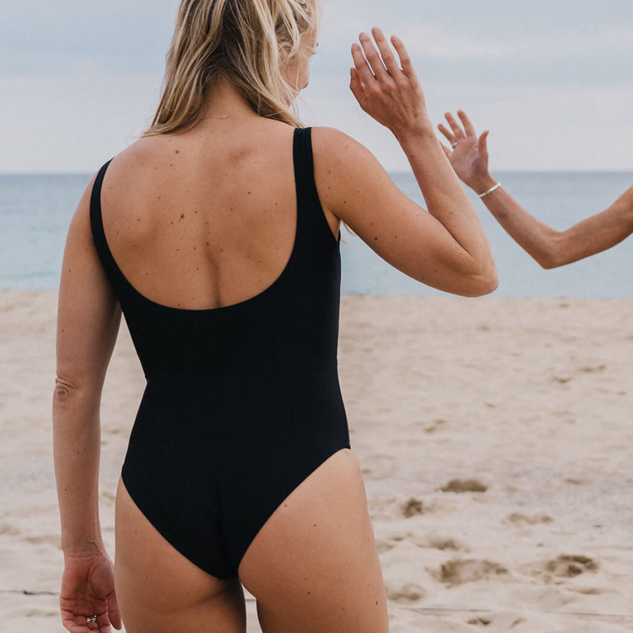 """Woman wearing black WONDA swimsuit """"Claudia"""" with a back cut at the beach"""